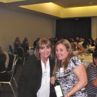 Travel Bulletin Publisher Jeanette Ratcliffe (left) presents Caribbean Bingo winner Nathalie Jenkins Flight Centre (right) with her prize of a bottle of wine