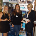 Emma Colyer (left) from Air Mauritius and Sharon Jones (right) from Sunset Faraway present Laura Clarke from Global Independent Travel with her prize - a bottle of Champagne and a box of chocolates.