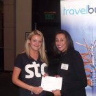 Melissa di Santo, STA Travel winning a 2 night stay at a Caesars Entertainment Resort, handing the prize over is Henika Patel, Regional sales Manager from Caesers Entertainment