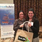 Nina Farrimond, Trade Relations Manager of South African Tourism presents 2 bottles of South African wine to Anita Kelsey Delmar World Travel