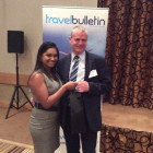 Lucy D'Silva Leisure Accounts Manager of South African Airways presents Paul Baxter from Thomson with an onboard bottle of wine.